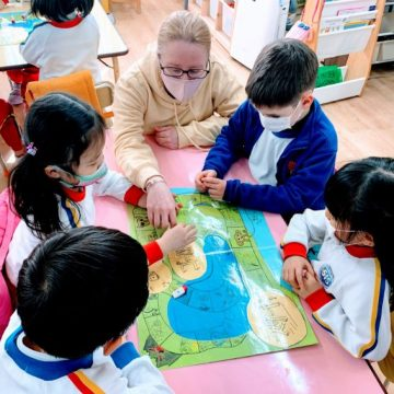 Kindergarten students and their teacher play board game in classroom