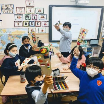 Grade 3 students and their teacher play board game in classroom