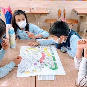 Grade 2 students and their teacher play board game in classroom